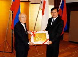 荒木浩FEC副会長に記念品を贈るラオス首相(右)