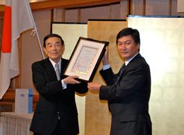 ジグジット大使から金川会長(左)に勲章・勲記の伝達