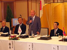 立って講演する藤井財務相、その右は金川FEC会長、左は笹森副議長