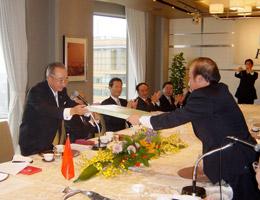 武藤委員長(左)が大使に記念品を贈る